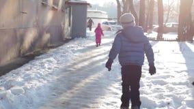 Περίπατος παιδιών στο χιόνι το χειμώνα στην ηλιόλουστη ημέρα τρεξίματα αγοριών στο χιόνι φιλμ μικρού μήκους