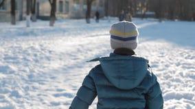 Περίπατος παιδιών στο χιόνι το χειμώνα στην ηλιόλουστη ημέρα τρεξίματα αγοριών στο χιόνι απόθεμα βίντεο