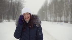 Περίπατος στο καθαρό αέρα Νέα γυναίκα που μιλά στο τηλέφωνο στο πάρκο απόθεμα βίντεο