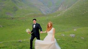 Περίπατος Enamored newlyweds στο λιβάδι ενάντια στο σκηνικό των όμορφων βουνών φιλμ μικρού μήκους