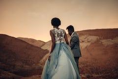 Περίπατος Newlyweds στο φαράγγι στο ηλιοβασίλεμα στοκ εικόνες