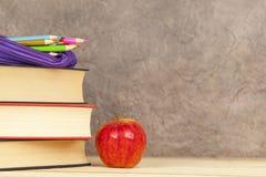 Περίπτωση μολυβιών σε έναν σωρό των βιβλίων με ένα μήλο Στοκ εικόνα με δικαίωμα ελεύθερης χρήσης
