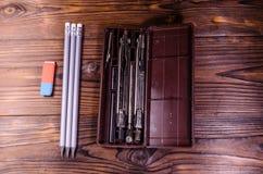 Περίπτωση τα όργανα, τα μολύβια και τη γόμα στον ξύλινο πίνακα στοκ φωτογραφία