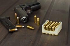 Περίστροφο με τα πυρομαχικά σε έναν σκοτεινό ξύλινο πίνακα Πωλήσεις των όπλων και των πυρομαχικών Διαφήμιση στα πυρομαχικά Στοκ εικόνες με δικαίωμα ελεύθερης χρήσης