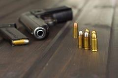 Περίστροφο με τα πυρομαχικά σε έναν σκοτεινό ξύλινο πίνακα Πωλήσεις των όπλων και των πυρομαχικών Διαφήμιση στα πυρομαχικά Στοκ Φωτογραφία