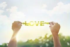 Περίληψη, που κρατά ένα πράσινο φύλλο στην αγάπη λέξης στο δονούμενο ουρανό σύννεφων Στοκ φωτογραφία με δικαίωμα ελεύθερης χρήσης
