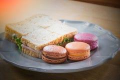 Περίληψη του ζωηρόχρωμου macaroon και σάντουιτς τυριού ζαμπόν έτοιμου να φάει Στοκ Φωτογραφίες