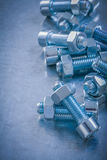 Περασμένος κλωστή screwbolts και καρύδια στο γρατσουνισμένο μεταλλικό υπόβαθρο ομο Στοκ φωτογραφία με δικαίωμα ελεύθερης χρήσης