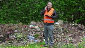 Περιβαλλοντικός ανώτερος υπάλληλος που μιλά στο έξυπνο τηλέφωνο στο μολυσμένο πάρκο απόθεμα βίντεο