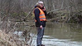 Περιβαλλοντικός επιθεωρητής με το smartphone κοντά στον ποταμό φιλμ μικρού μήκους