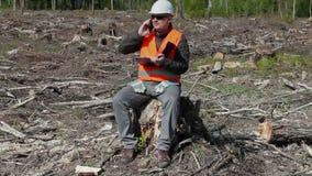 Περιβαλλοντικός επιθεωρητής που μιλά στο έξυπνο τηλέφωνο στο δάσος απόθεμα βίντεο
