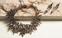 Περιδέραιο και σκουλαρίκια που τίθενται στη φυσική πέτρα Στοκ φωτογραφία με δικαίωμα ελεύθερης χρήσης