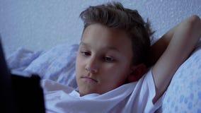 Περιεχόμενο μέσων προσοχής αγοριών εφήβων στην ταμπλέτα που βρίσκεται στο σπίτι απόθεμα βίντεο