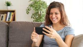 Περιεχόμενο μέσων προσοχής κοριτσιών σε ένα έξυπνο τηλέφωνο στο σπίτι απόθεμα βίντεο