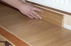 Περιζώνοντας πίνακας & Architrave Χέρια επισκευαστών που εγκαθιστούν το περιζώνοντας δρύινο ξύλινο πάτωμα πινάκων με την κόλλα Δά Στοκ φωτογραφίες με δικαίωμα ελεύθερης χρήσης