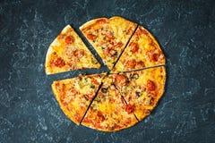 Περικοπή στην εύγευστη φρέσκια πίτσα φετών με τις ντομάτες και ελιά σε ένα σκοτεινό υπόβαθρο Τοπ όψη Πίτσα στο μαύρο πίνακα Στοκ Φωτογραφία