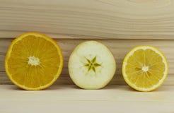 Περικοπών φρέσκος juicy φυσικός ξινός ασβέστης λεμονιών μήλων πορτοκαλής μισός στο ξύλινο υπόβαθρο Στοκ Φωτογραφία