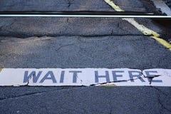 Περιμένετε εδώ το σημάδι στο πέρασμα σιδηροδρόμων στοκ εικόνα με δικαίωμα ελεύθερης χρήσης