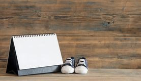 Περιμένοντας έννοια μωρών Παπούτσι και ημερολόγιο μωρών στο ξύλινο backgroun Στοκ Εικόνες