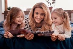Περιοδικά ανάγνωσης παιδιών και μητέρων από κοινού στοκ φωτογραφία