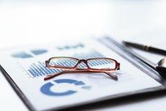 Περιοχή αποκομμάτων με την οικονομική έκθεση και γυαλιά σχετικά με τον υπολογιστή γραφείου στοκ φωτογραφία