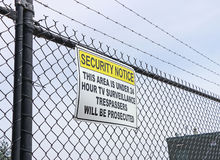 Περιοχή κάτω από το προειδοποιητικό σημάδι επιτήρησης στο φράκτη καλωδίων Στοκ Εικόνες