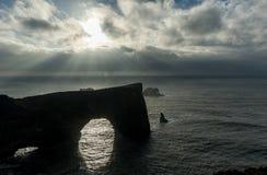 Περιοχή Dyrholaey στην Ισλανδία Κοντά στη μαύρη παραλία άμμου Ανατολή νεφελώδης ουρανός Φως του ήλιου επάνω από το νερό Στοκ Εικόνες