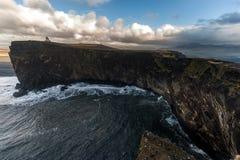 Περιοχή Dyrholaey στην Ισλανδία Κοντά στη μαύρη παραλία άμμου Ανατολή Φάρος στο υπόβαθρο Στοκ εικόνες με δικαίωμα ελεύθερης χρήσης