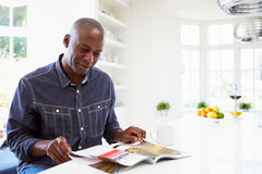 Περιοδικό ανάγνωσης ατόμων αφροαμερικάνων στο σπίτι στοκ εικόνα με δικαίωμα ελεύθερης χρήσης