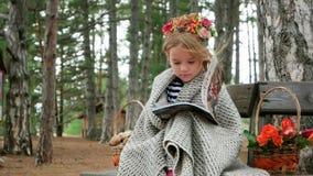 Περιοδικό ανάγνωσης μικρών κοριτσιών, παιδί στη συνεδρίαση κάλυψης στον πάγκο με το βιβλίο, κρύος αέρας φθινοπώρου, ψάθινο καλάθι απόθεμα βίντεο