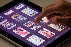 Περιοδικό ανάγνωσης που χρησιμοποιεί μια ταμπλέτα Στοκ εικόνα με δικαίωμα ελεύθερης χρήσης