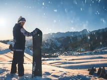 Περιπέτεια στο χειμερινό αθλητισμό Κορίτσι Snowboarder στο υψηλό βουνό υποβάθρου στοκ εικόνα