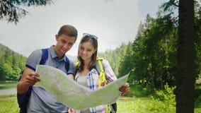 Περιπέτειες στα βουνά Οι νέοι τουρίστες εξετάζουν το χάρτη θέσης τους απόθεμα βίντεο