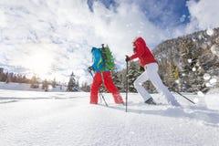 Περιπατητές πλεγμάτων σχήματος ρακέτας που τρέχουν στο χιόνι σκονών με το όμορφο φως ανατολής στοκ εικόνες