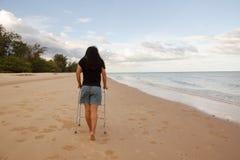 Περιπατητής χρήσης γυναικών στην παραλία άμμου Στοκ εικόνες με δικαίωμα ελεύθερης χρήσης