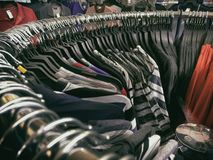 Περιστασιακές μπλούζες που κρεμούν στο κυρτό ράφι Στοκ φωτογραφία με δικαίωμα ελεύθερης χρήσης