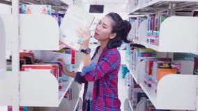 Περιστασιακή γυναίκα που επιδιώκει το βιβλίο στη βιβλιοθήκη φιλμ μικρού μήκους