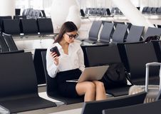 Περιστασιακή γυναίκα που εργάζεται στο lap-top στην αίθουσα αερολιμένων Γυναίκα που περιμένει την πτήση του στο τερματικό αερολιμ στοκ φωτογραφίες