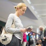 Περιστασιακή γυναίκα που περιμένει την πτήση της στον αερολιμένα Στοκ Εικόνες