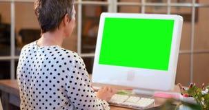 Περιστασιακή επιχειρηματίας που χρησιμοποιεί τον υπολογιστή με την πράσινη οθόνη φιλμ μικρού μήκους