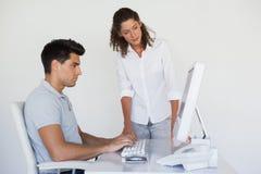 Περιστασιακή επιχειρησιακή ομάδα που εξετάζει τον υπολογιστή μαζί στο γραφείο Στοκ φωτογραφία με δικαίωμα ελεύθερης χρήσης