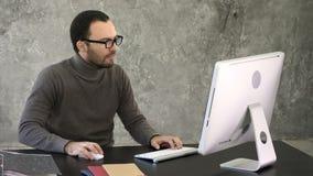 Περιστασιακή εργασία επιχειρηματιών στην αρχή, καθμένος στο γραφείο, δακτυλογραφώντας στο πληκτρολόγιο, που εξετάζει τη οθόνη υπο απόθεμα βίντεο
