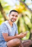 Περιστασιακή ευτυχής δακτυλογράφηση ατόμων στη συνεδρίαση smartphone σε έναν πάγκο σε ένα πάρκο στοκ φωτογραφία με δικαίωμα ελεύθερης χρήσης