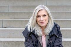 Περιστασιακή μέσης ηλικίας συνεδρίαση γυναικών στα υπαίθρια βήματα στοκ εικόνα