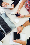 Περιστασιακοί ανώτεροι υπάλληλοι που χρησιμοποιούν τα διαφορετικά ηλεκτρονικά αντικείμενα σε ένα meetin Στοκ φωτογραφία με δικαίωμα ελεύθερης χρήσης