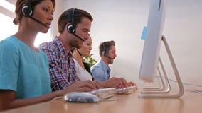 Περιστασιακοί επιχειρηματίες που εργάζονται στο τηλεφωνικό κέντρο απόθεμα βίντεο