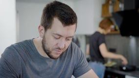 Περιστασιακός άνδρας στην κουζίνα με τη γυναίκα απόθεμα βίντεο