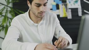 Περιστασιακός αρσενικός σχεδιαστής που χρησιμοποιεί την ταμπλέτα γραφικής παράστασης σε ένα φωτεινό γραφείο απόθεμα βίντεο