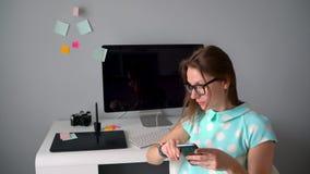 Περιστασιακός γραφικός σχεδιαστής που μιλά στο τηλέφωνο κατά τη διάρκεια ενός καφές-σπασίματος στο δημιουργικό γραφείο απόθεμα βίντεο