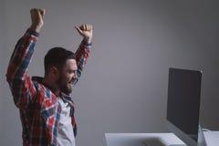 Περιστασιακός επιχειρηματίας ενθαρρυντικός μπροστά από τον υπολογιστή του στο γραφείο στοκ φωτογραφία με δικαίωμα ελεύθερης χρήσης